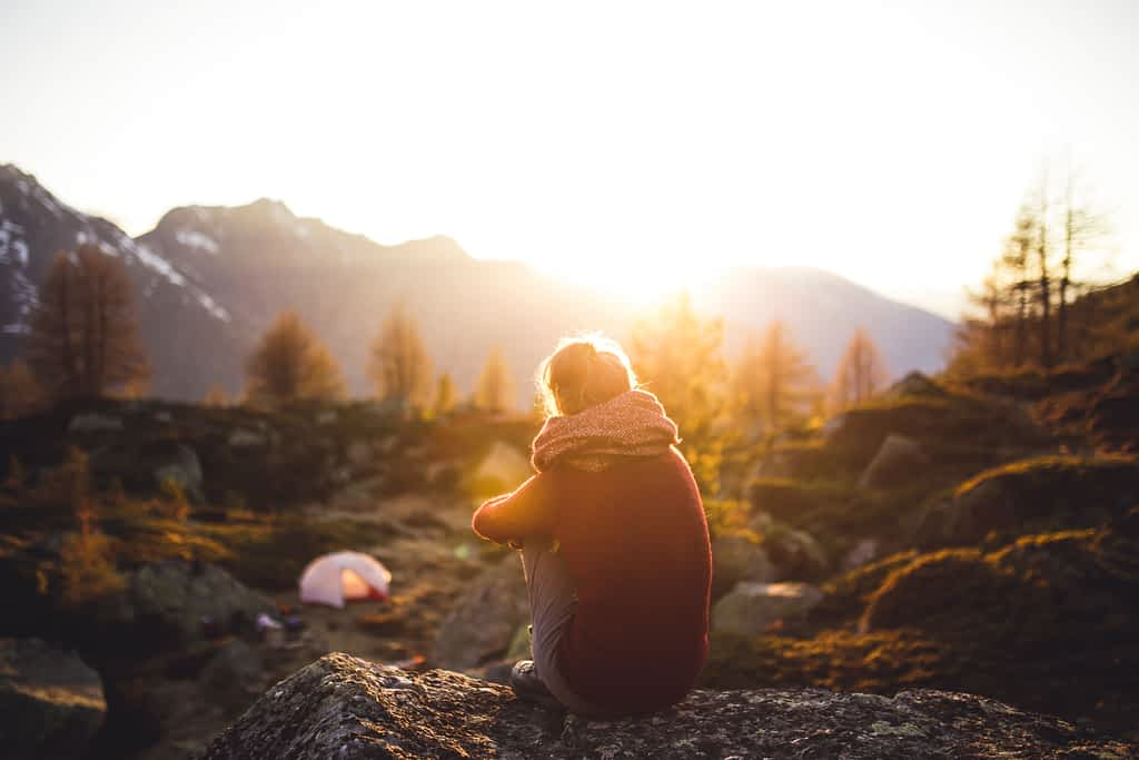 A person sitting and looking at a mountain and sunset