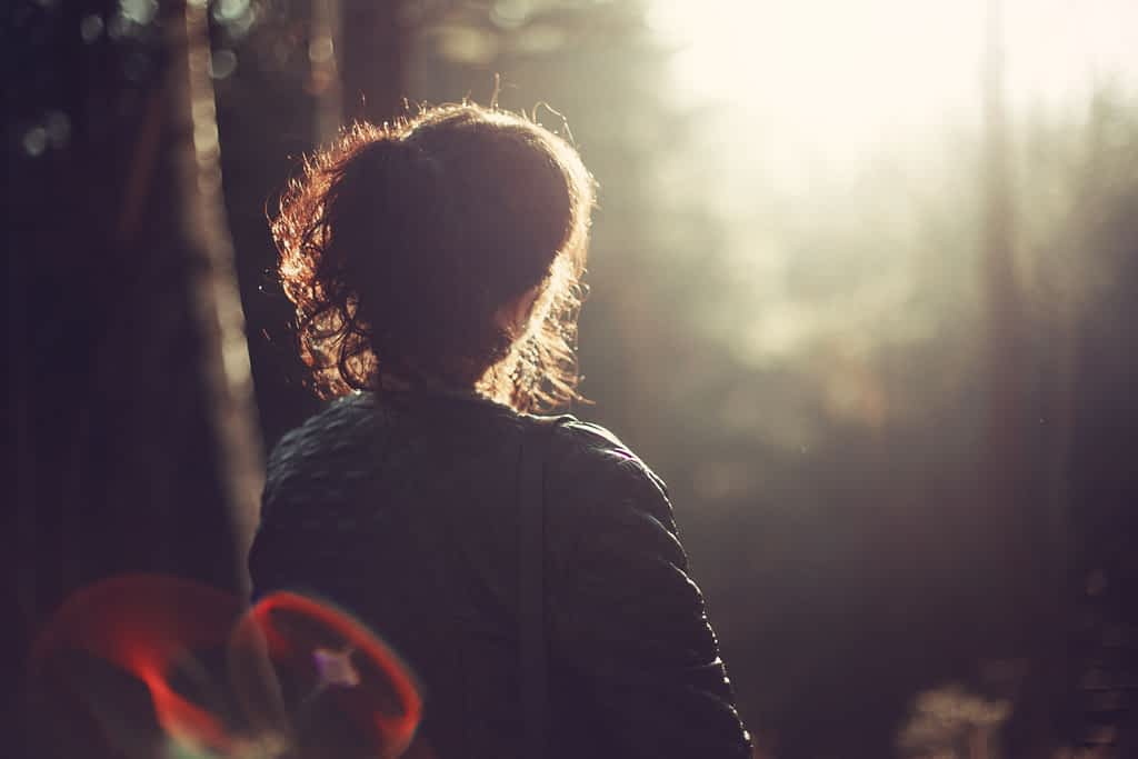 Silhouette of a woman standing in a forest