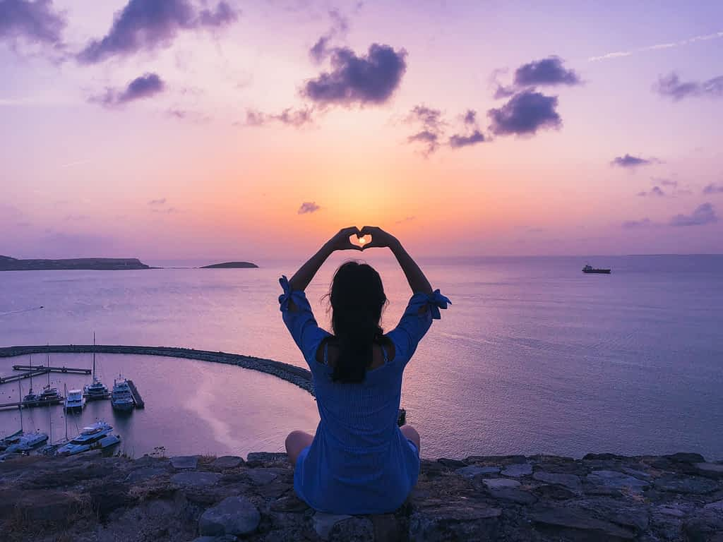 A woman sitting on a rock doing a heart shape gesture with her fingers