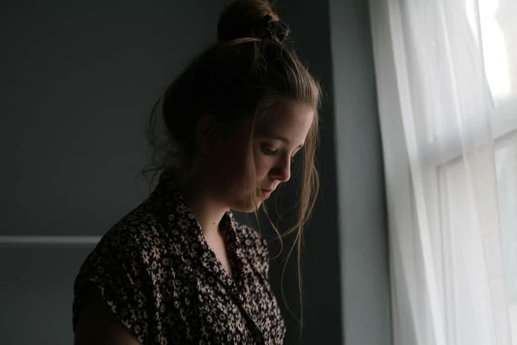 A woman standing beside a curtain window