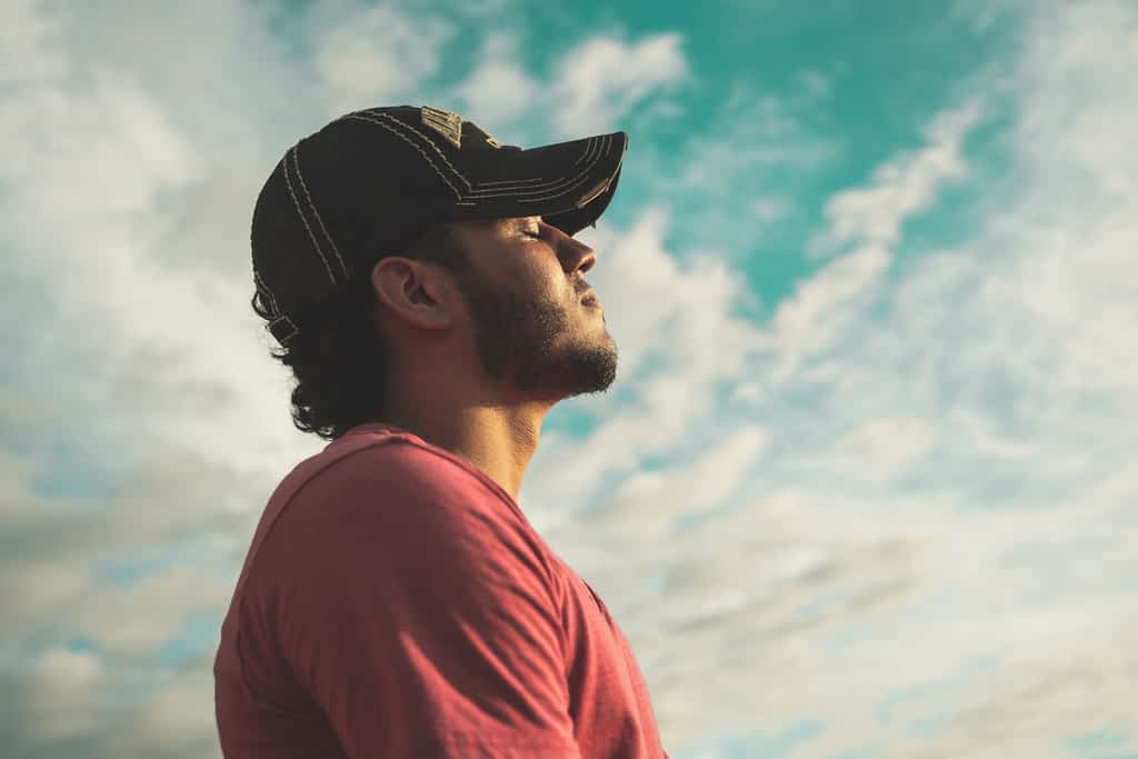 A man wearing a cap and looking at the sky with his eyes closed