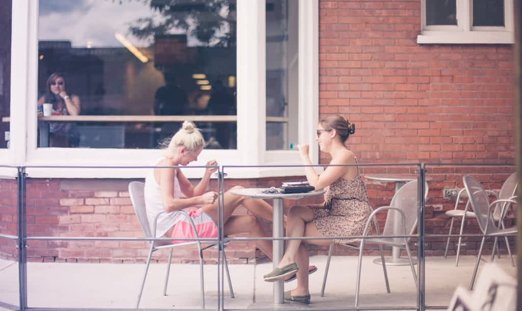 Two women sitting at a cafe and talking