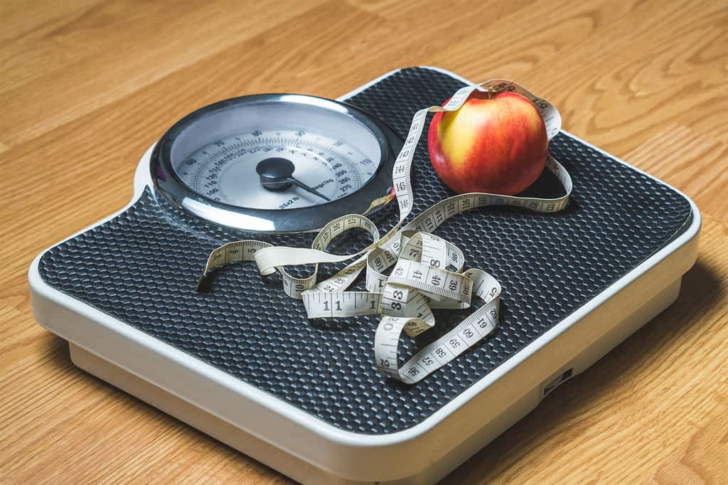 A scale with a measuring tape and apple on top