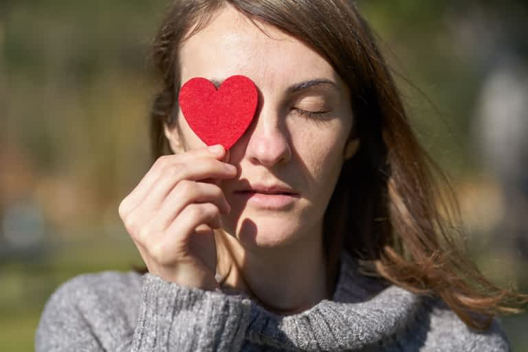 A woman holding a heart shaped cut out over one eye
