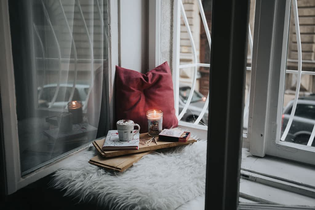 Windowsill with a pillow, candle and a journal