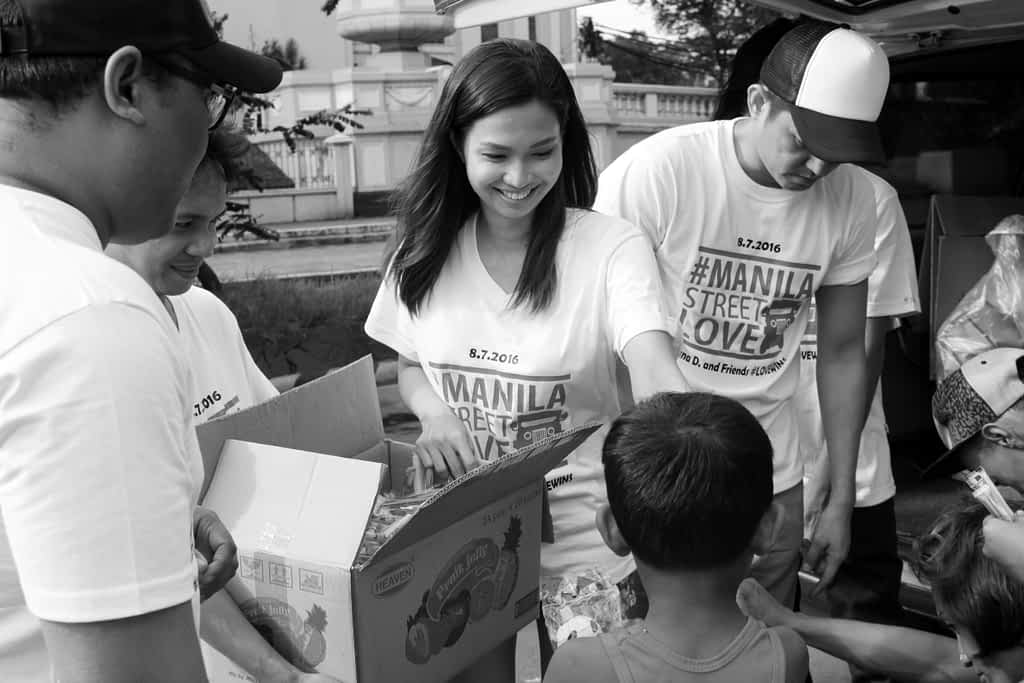 Adult volunteers handing out food to children