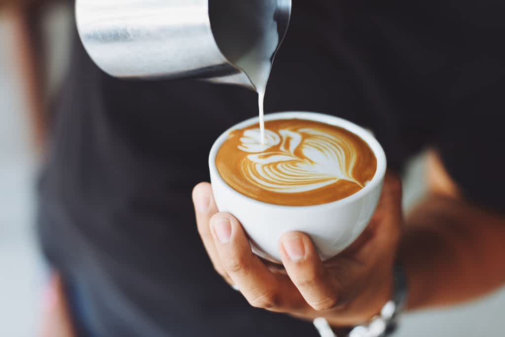 A barista pouring milk into a cup of coffee