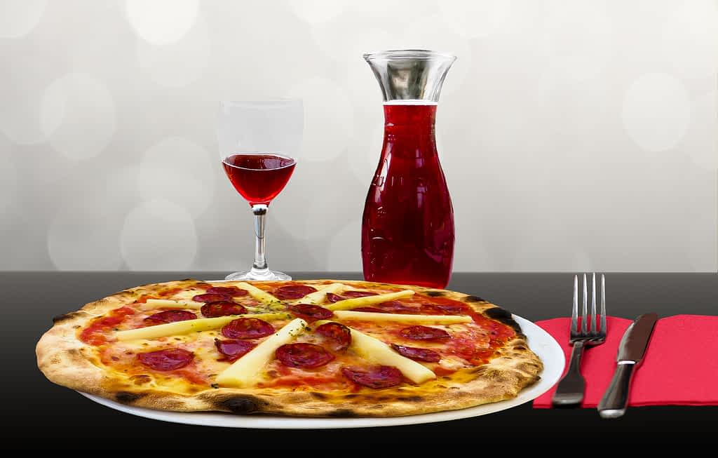A pepperoni pizza and a flask of red wine