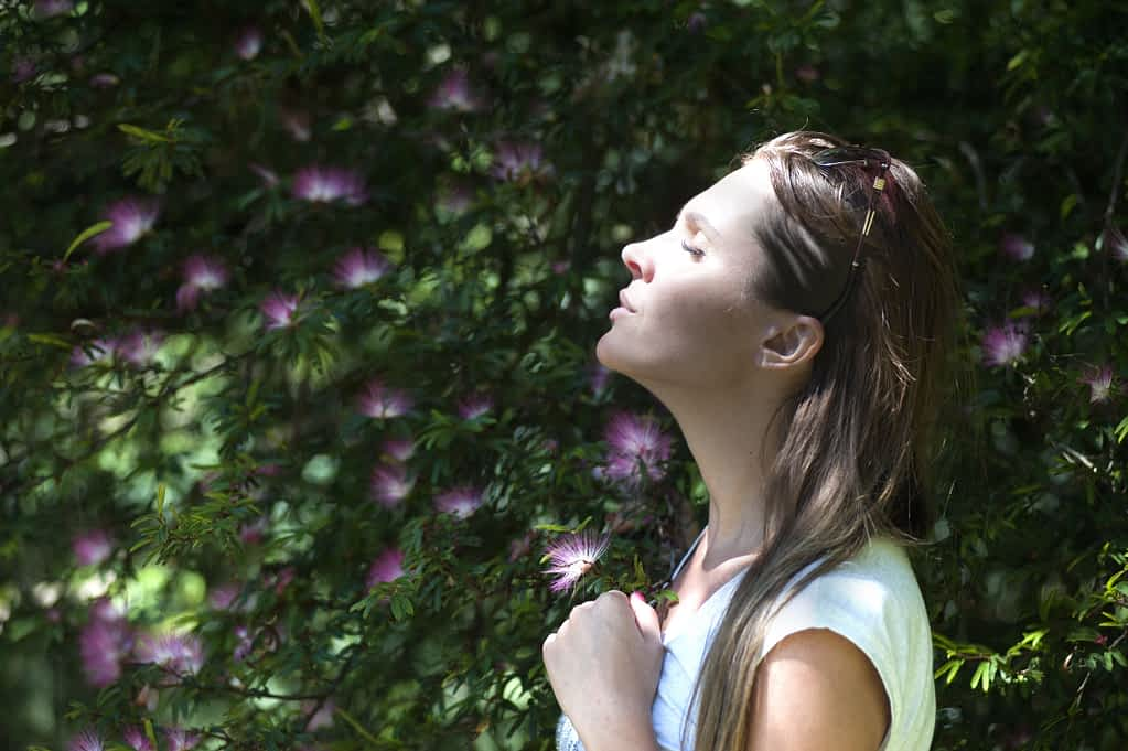 A woman taking a deep breath in nature