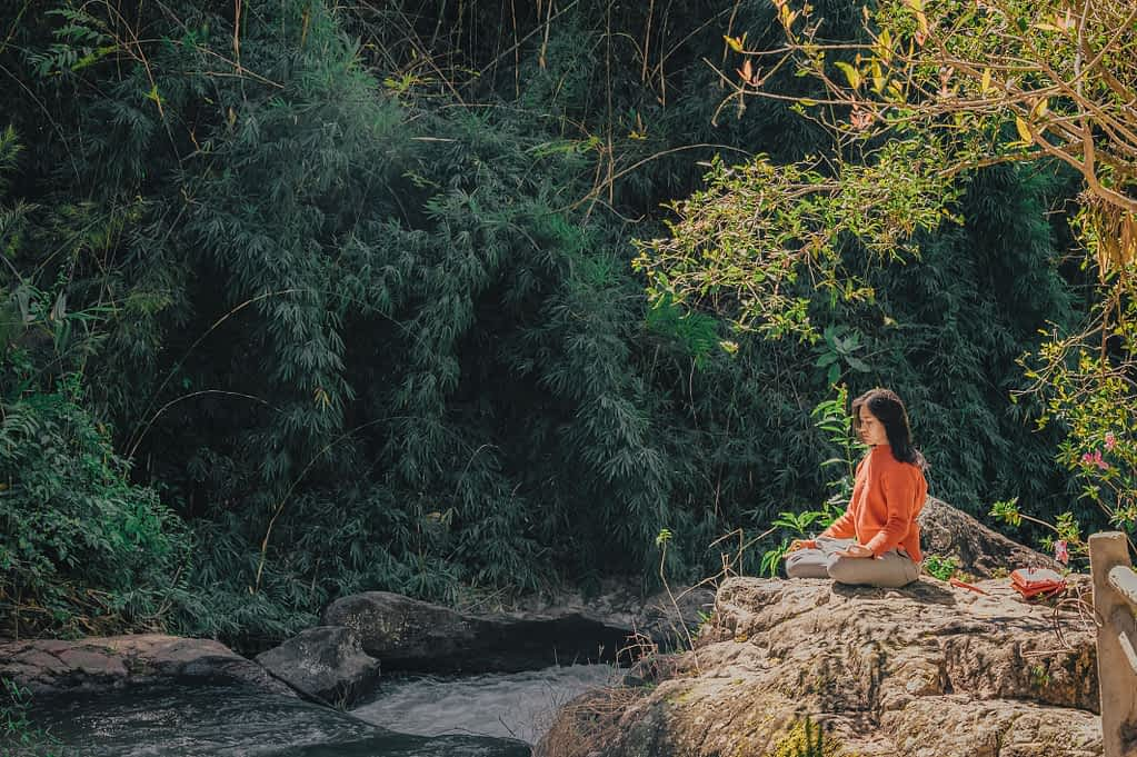 Woman sitting on a stone near a stream