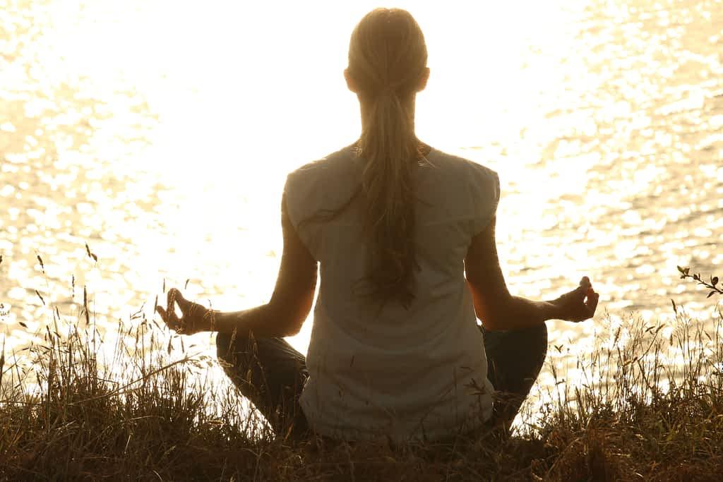 A woman meditating by a lake