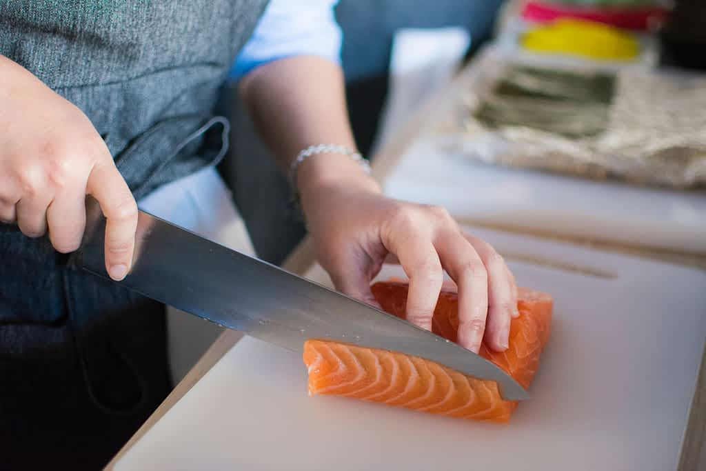 Person slicing salmon on a cutting board
