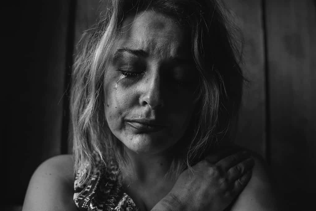 A woman crying and feeling grief and loss