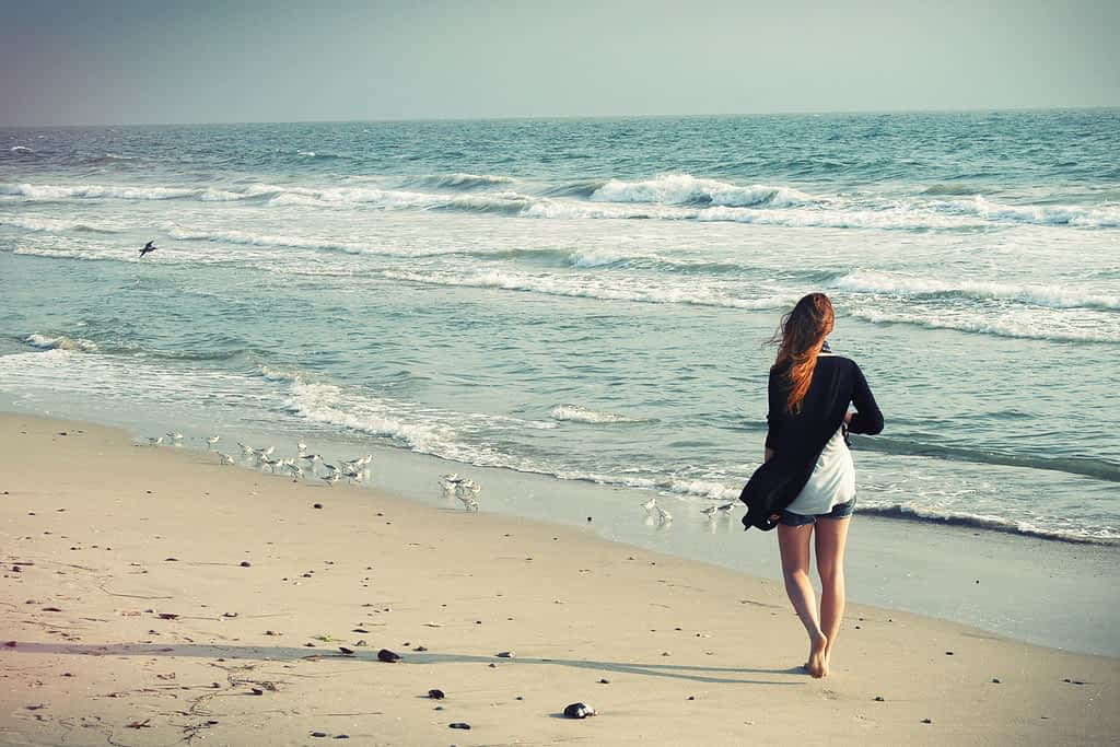 A woman walking alone on the beach