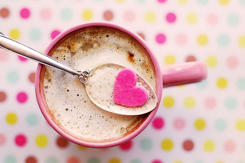 A cup of hot coco with a spoon and a heart shaped cookie