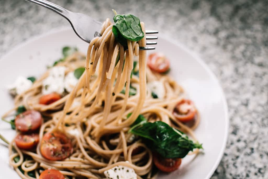 A bowl of pasta with tomatoes and basil