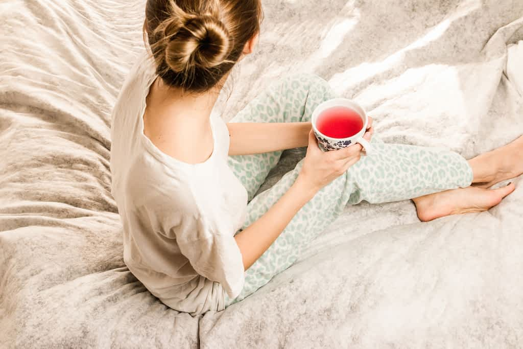 A woman sitting on her bed holding a cup of tea and practicing self-care