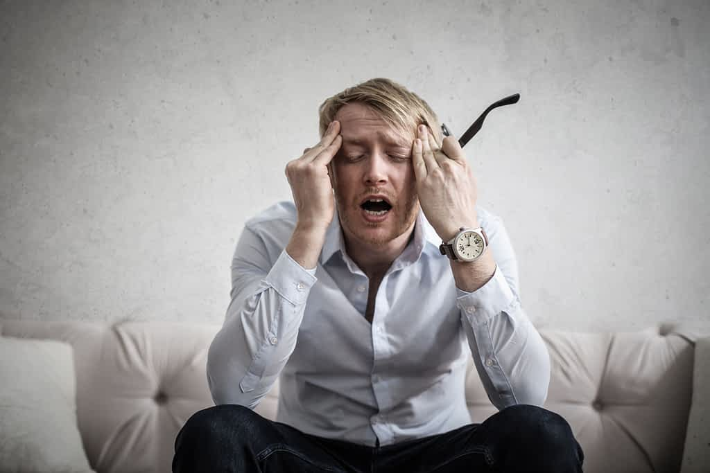 Photo of a man touching his head because he is anxious