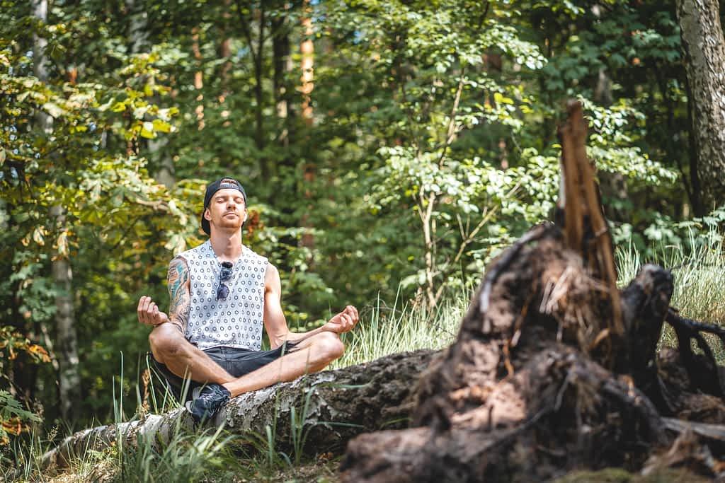 A man meditating on a tree log