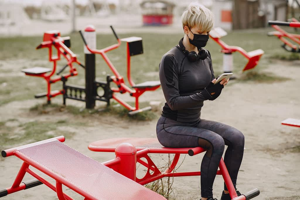 Woman in a mask exercising outdoors