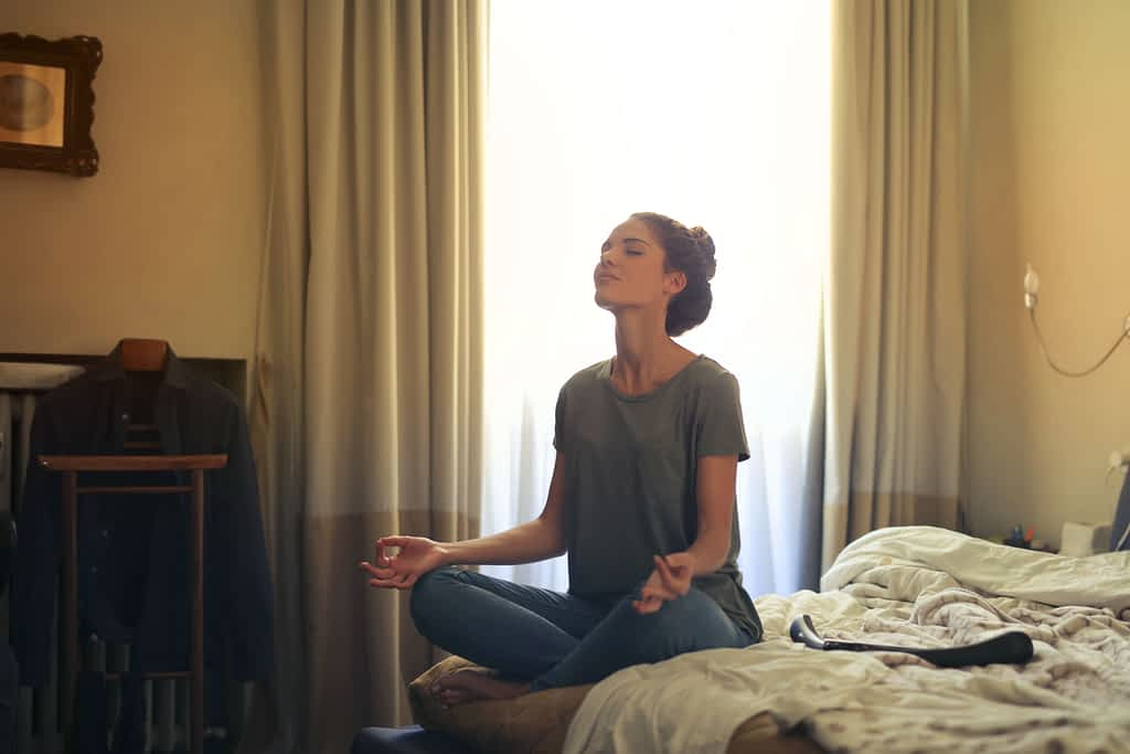 Woman practicing meditation on her bed
