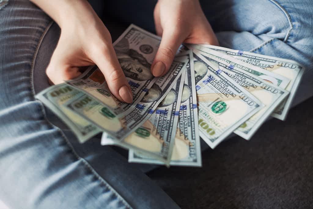 A person holding several hundred dollar bills