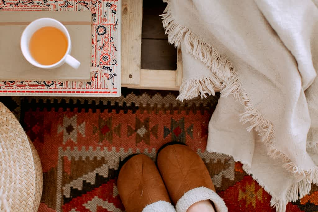 A pair of feet in cozy slippers next to a cup of tea and a blanket