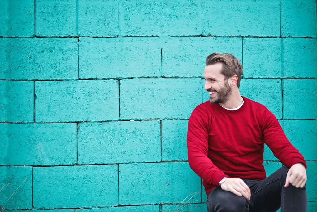 A man leaning on a wall and sitting on a bench smiling