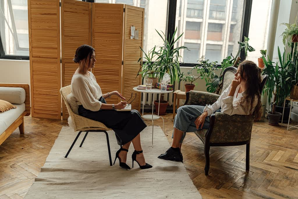 A woman starting therapy and meeting with therapist in her office sitting across from each other
