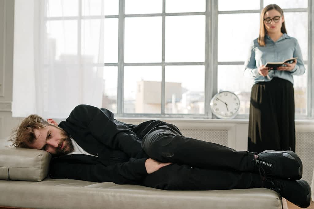 A man lying down on couch during his therapy session while his female therapist stands behind him near the window