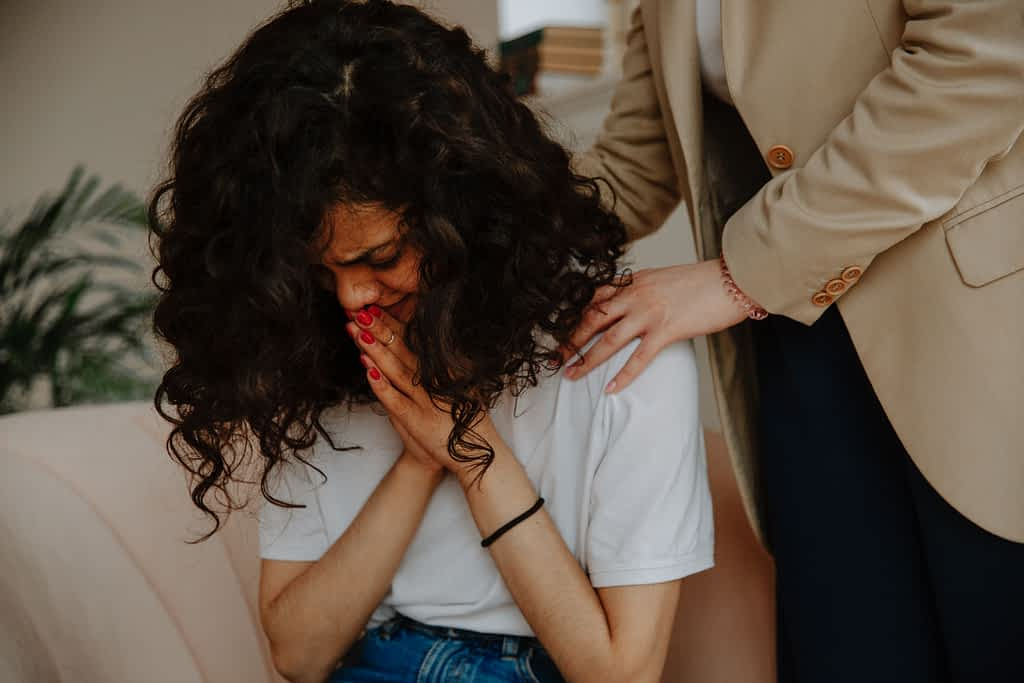 A woman crying while her therapist is touching her shoulder