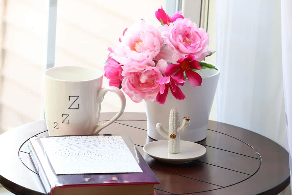 A mug next to a vase with roses and a notebook