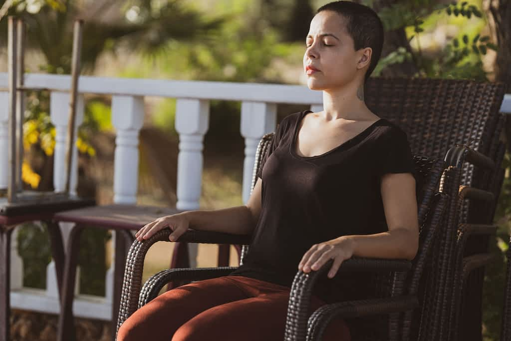 A woman meditating with her eyes closed on a chair outside on a deck