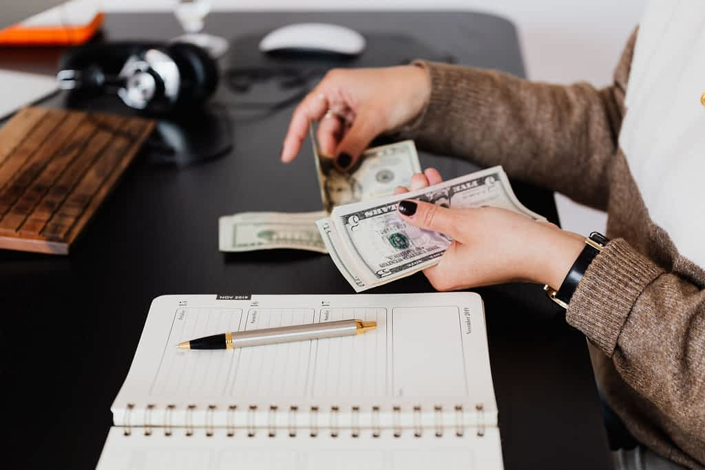 A person budgeting their money while holding cash int heir hand and writing down information in a notebook