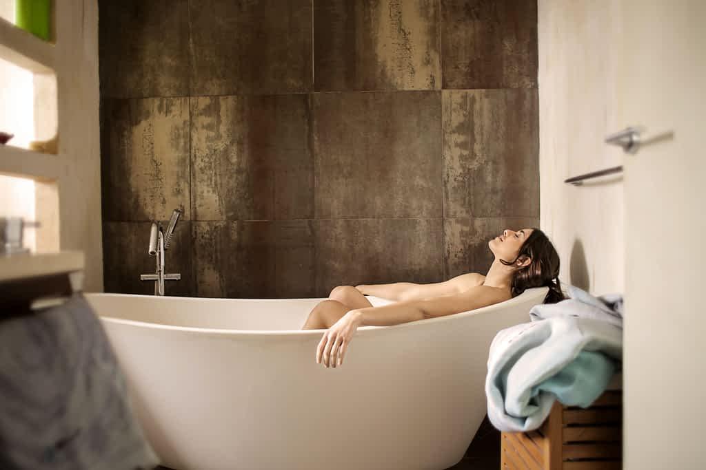 A woman lying down in a bathtub relaxing