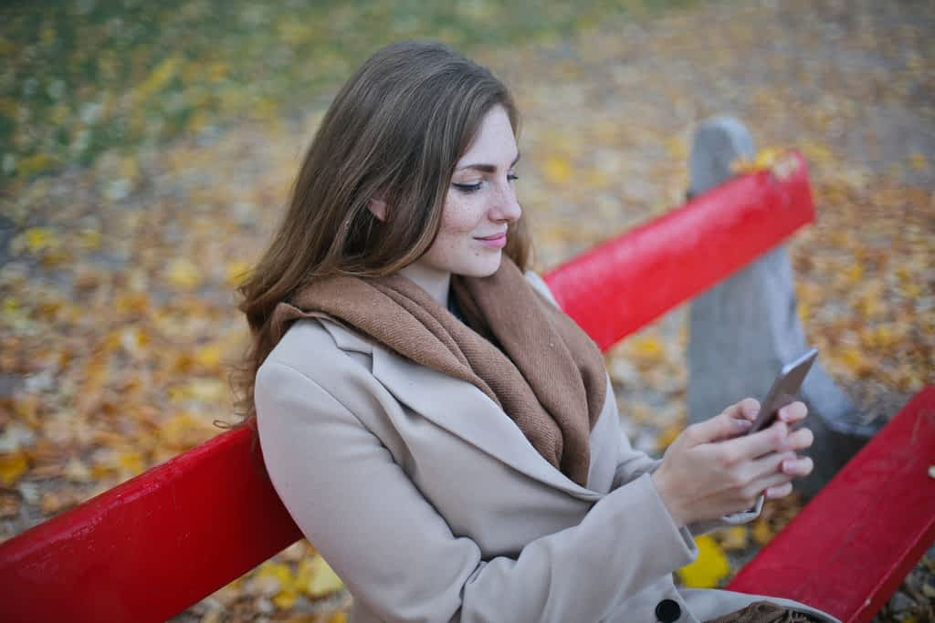 A woman sitting on a bench looking at her phone