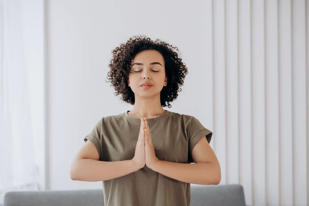 A woman standing with her eyes closed and hands in prayer position