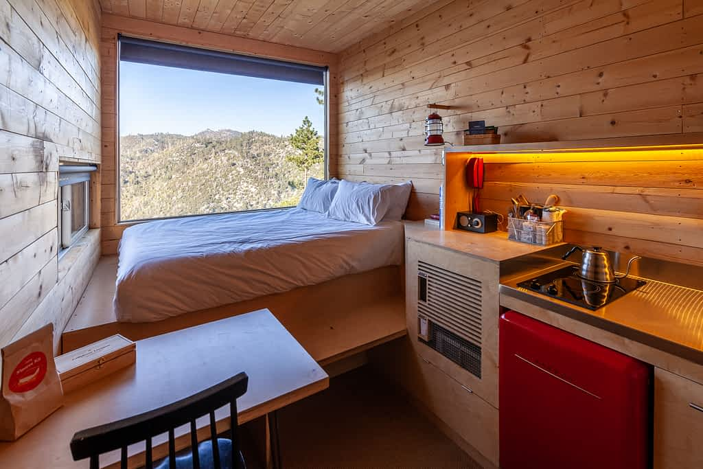 Getaway House Big Bear cabin interior with small kitchenette and chair