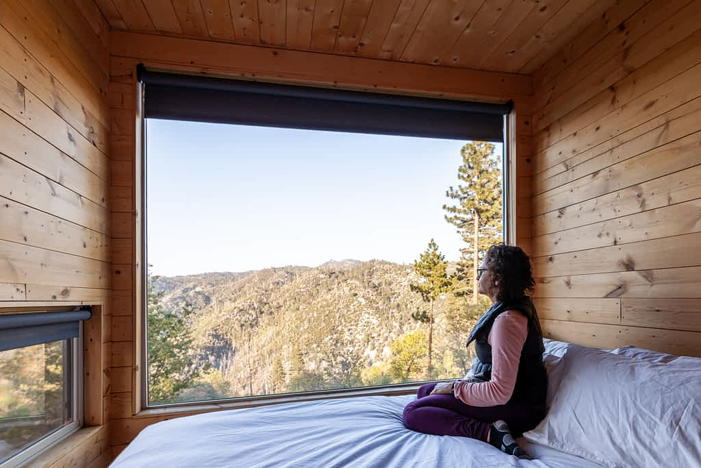 Getaway House Big Bear Pantea Rahimian looking outside while sitting on the bed