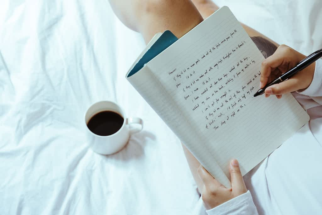 A person journaling on their bed with a cup of coffee beside them