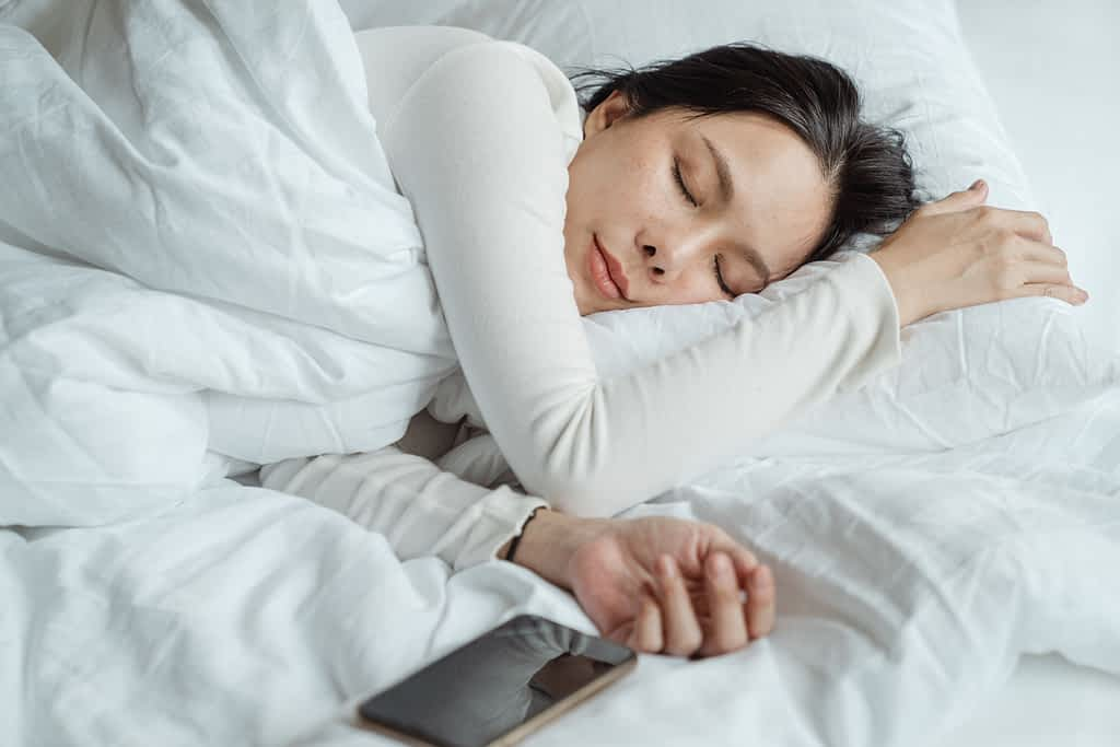 A woman sleeping in bed wih her phone next to her