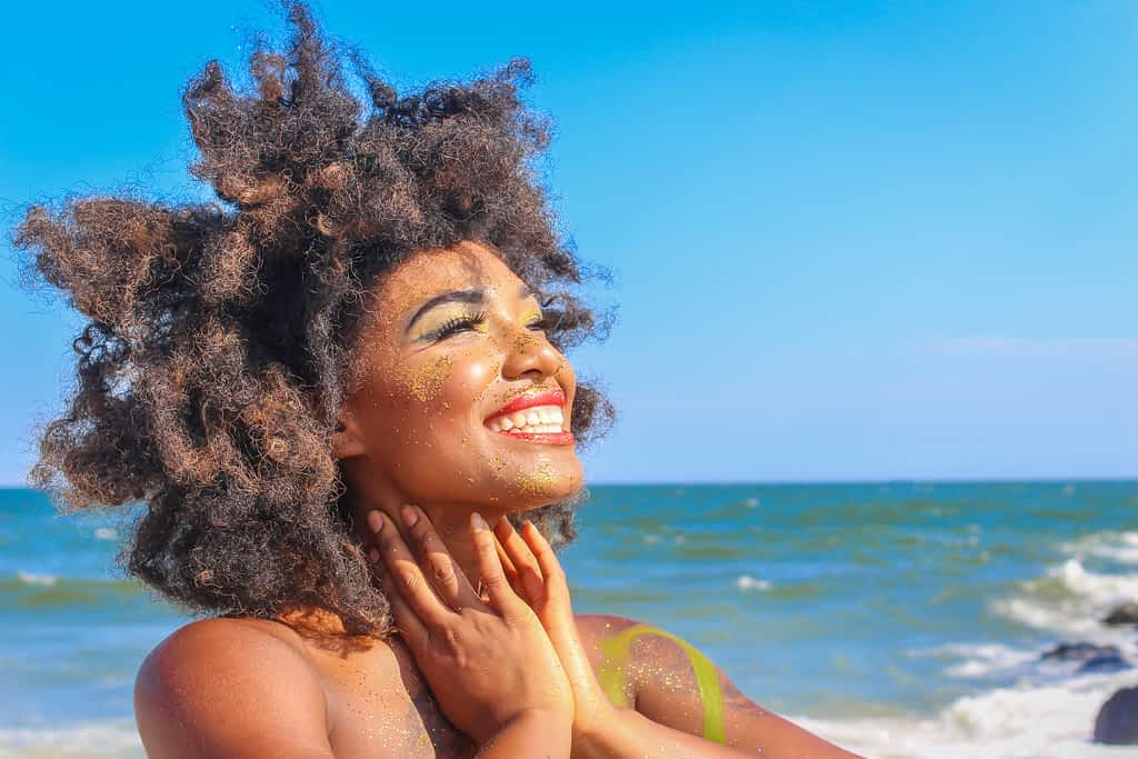 How to be happy: a beautiful woman smiling on the beach