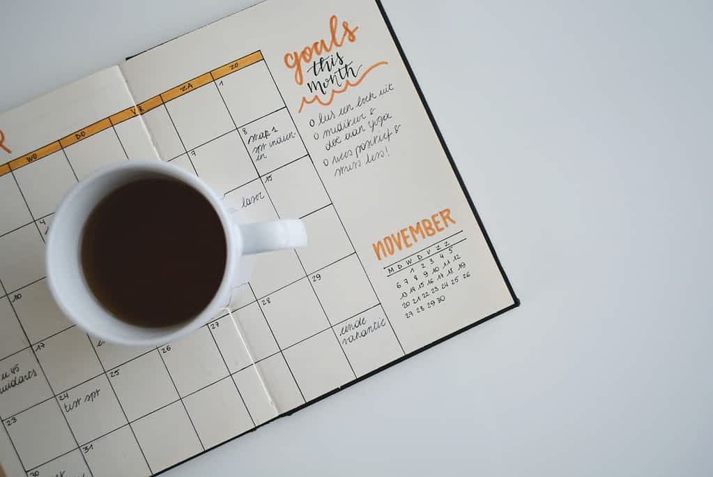 A schedule with a cup of coffee on top of it