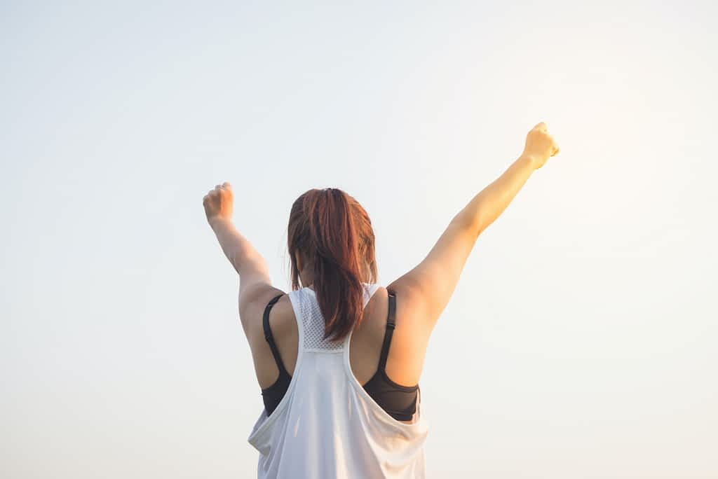 The back of a woman with her arms raised up in a V
