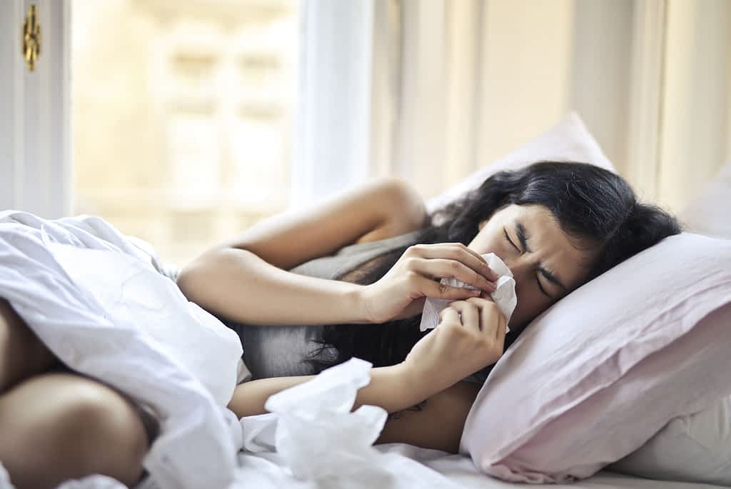 A woman sneezing in bed during pandemic winter