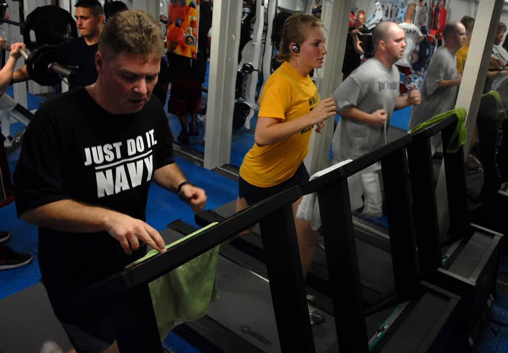 Three people walking on treadmills in a gym