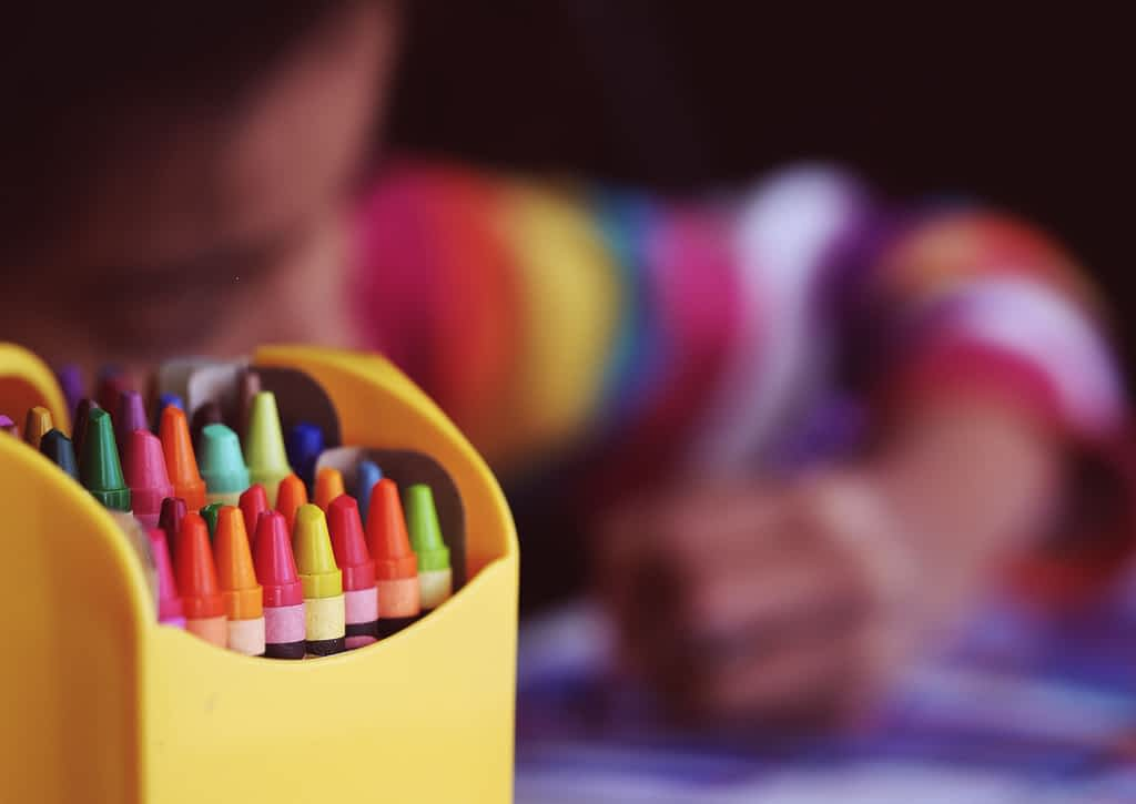 A box of crayons next to a child drawing during the coronavirus lockdown