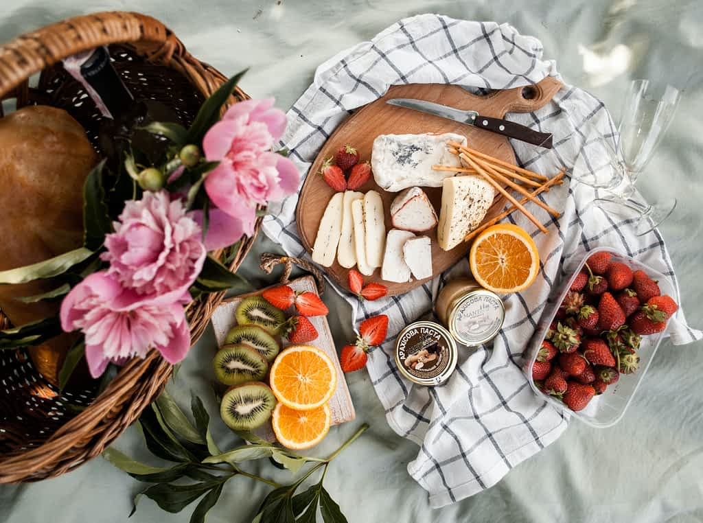 Variety of fruits and cheese on a picnic blanket