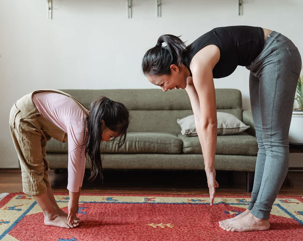 A mother and daughter stretching together at home