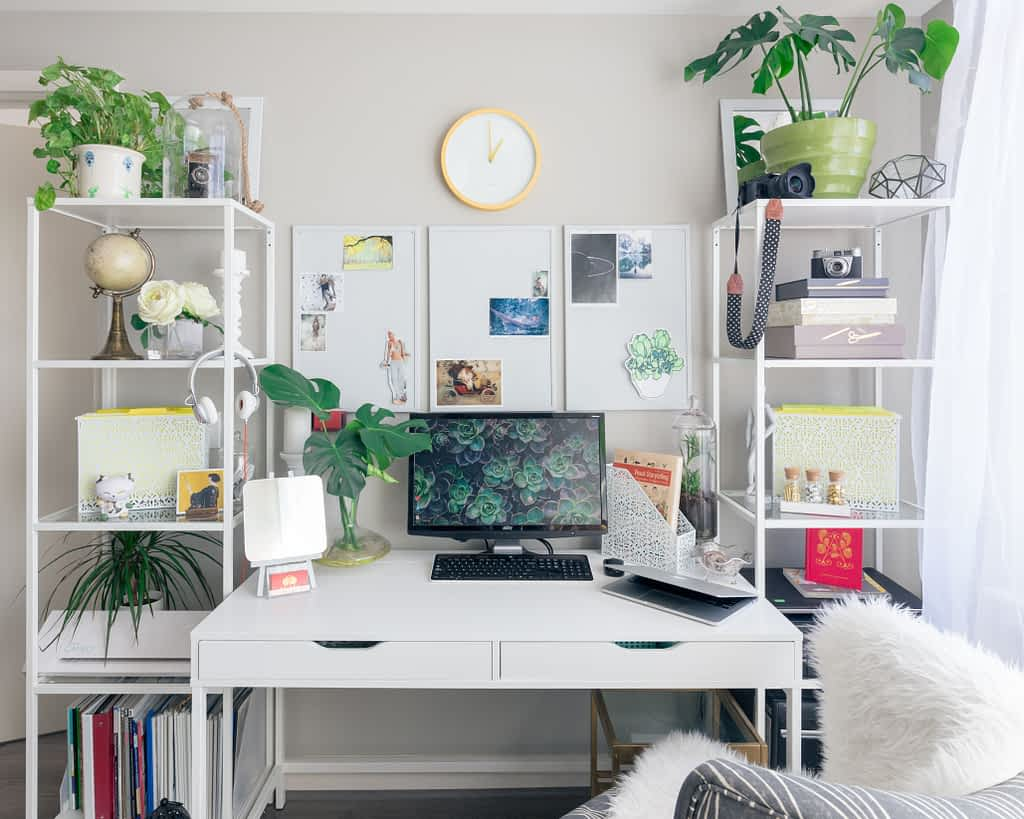 A desk with a desktop computer and lots of plants